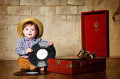 Little boy sitting with a plate near the gramophone. — Stock Photo