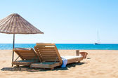 Sunbeds and rattan parasols on sandy seaside. — Foto Stock