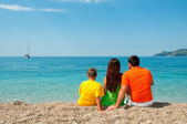 Happy family: Mom, Dad and son sitting on the beach, looking into distance — Stock Photo