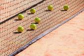 Tennis balls on the court near tennis nets — Stock Photo