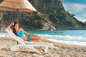 Beautiful brunette girl sunbathing on a sunbed  at  the sea — Stock Photo