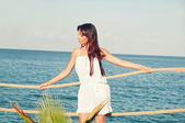 Girl with long hair in a short white dress on the pier — Stock Photo