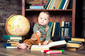 Menino bonito, sentado com a globo, livros e lápis de desenho — Fotografia Stock