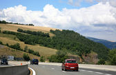 Scenic road and cars between green mountains — Stock Photo