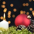 Red Christmas baubles and candle on black background of defocused golden lights. — Stock Photo