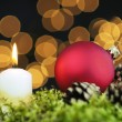Red Christmas baubles and candle on black background of defocused golden lights. — Stock fotografie