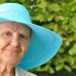 Senior woman in blue hat outdoors in garden. — Stock Photo