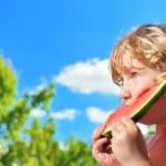 Lttle girl eating watermelon on the blu sky. — Stock Photo