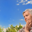 Senior woman - thinking, outdoors. — Stock Photo #18935819