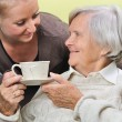 Senior woman with caregiver at home. - Stock Photo