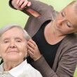 Senior woman with her caregiver in home. - Stock Photo