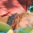 Stock Photo: Child sleeps in a hammock in the garden.