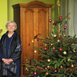 Elderly woman stands next to a Christmas tree in the room. — Stock Photo