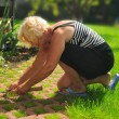 Mature woman working in garden. — Stock Photo