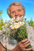 Senior woman smelling flowers on blue sky. — Stock Photo