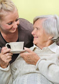 Senior woman with caregiver at home. — Stock Photo