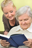 Senior woman with her caregiver in home reading book. — Stock Photo