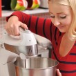 Young blonde woman using a mixer in red kitchen. — Stock Photo