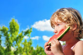 Lttle girl eating watermelon on the blu sky. — Stock Photo