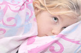 Child lying in bed with a pink quilt. — Stock Photo