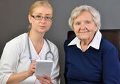 Elderly woman and a young doctor. — Stock Photo