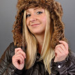 Young, pretty, blond woman in fur cap looks into the camera. — Stock Photo