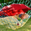 Child sleeps in a hammock in the garden. — Stock Photo #19071501