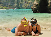 Happy couple on the beach dressed in snorkelling. — Stock Photo
