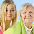 Child and grandchild give a gift senior woman. — Stock Photo #24960921