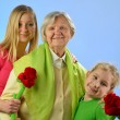 Child and grandchild give a gift senior woman. — Stock Photo
