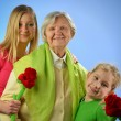 Stock Photo: Child and grandchild give gift senior woman.