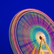 Carousel. Ferris Wheel on a blue background. Long time exposure. - Stok fotoğraf