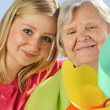 Stock Photo: Child and grandchild give a gift senior woman.