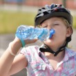 Young girl in a bicycle helmet drinking water. — Stock Photo