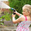 Young girl watering plants in the garden. — Stock Photo