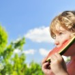 Little girl eating melon outdoors. — Stock Photo #40501497