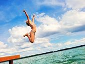 Girl jumping into the lake. — Stock Photo
