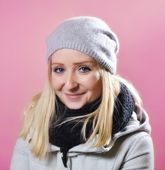 Young woman in warm clothes on a pink background. — Stock Photo