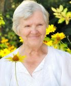 Senior woman in garden full of flowers. — Stock Photo