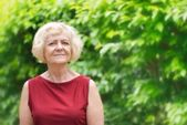 Mature, blonde woman in garden, — Stock Photo
