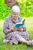 Senior woman reading book in park. — 图库照片