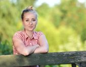 Młoda atrakcyjna kobieta stojąc na drewnianym tarasem. — Zdjęcie stockowe