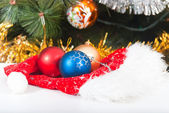 Hat of Santa Claus and balls on Christmas tree background — Stock Photo