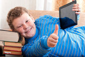 Boy with a tablet computer is on the books — Stock Photo