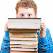 Surprised boy looks out from behind a pile of books — Stock Photo #21290861