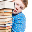 Sad boy looks out from behind a pile of books - Stock Photo
