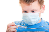 A boy in a protective mask with thermometer in hand — Stock Photo