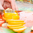 Woman's hand are cut lemon on a cutting board - Stock Photo