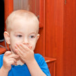 Portrait of a young child closing mouth with his hand — Stock Photo