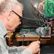 Stock Photo: Elderly mrepairing old TV